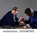 Small photo of Businessmen fight for leadership. Confrontation of business leaders. Winner and defeated concept. Men in suit or businessmen with aggressive faces compete in armwrestling on table on dark background.