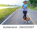 Stock photo girl outdoors on road with her dog 1061522507