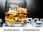whiskey in a glass of ice on a... | Shutterstock . vector #1062046223