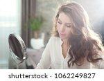 woman looking in little mirror... | Shutterstock . vector #1062249827