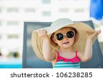 Portrait of baby in hat and glasses sitting on sun bed - stock photo