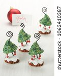 Small photo of Whimsical Christmas tree placard holders with swirl and red accents and red ball ornaments.