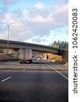Small photo of Big rig semi truck with dry van semi trailer going under the bridge across multiline divided highway at sunny day with cloudy blue sky