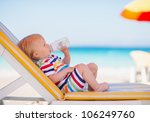 Portrait of baby on sunbed drinking water - stock photo