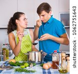 Small photo of Surprised husband and wife feeling foul smell of food from casserole