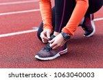 woman runner tying shoelace on... | Shutterstock . vector #1063040003