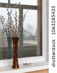 Small photo of Willow branches in a wooden vase on a window sill