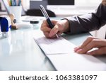 Small photo of Close-up Of A Businessperson's Hand Signing Cheque With Pen In Office