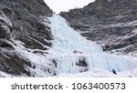 Small photo of male ice climber stands at the headwall of a long and steep waterfall in the Alps