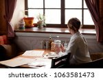 the girl sits in a cafe with a... | Shutterstock . vector #1063581473