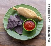Small photo of Tamale served with blue corn tortillas and tomato sauce top view