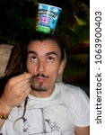 Small photo of Kaw/French Guiana - 03.20.2015: A weird looking rasta man is eating a delicious ice cream.