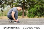 men knelt down to do up his... | Shutterstock . vector #1064037407