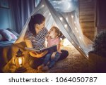 family bedtime. mom and child... | Shutterstock . vector #1064050787