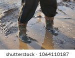a man in large dirty rubber... | Shutterstock . vector #1064110187