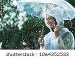 rainy day asian woman wearing a ... | Shutterstock . vector #1064352533