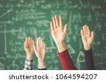 students raised up hands green... | Shutterstock . vector #1064594207