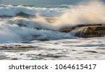 rocky seashore with wavy ocean... | Shutterstock . vector #1064615417