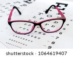 glasses on a eye exam chart to... | Shutterstock . vector #1064619407