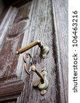 Closeup of an old wooden door with a big key in the lock - stock photo