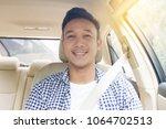 asian man sitting in car seat... | Shutterstock . vector #1064702513