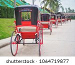 Small photo of Many red horse carriages are parked on the street for people to roam or travel to various places, Traditional transportation