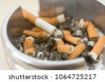 Small photo of Ashtray full of extinguished cigarette butts with one lit