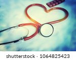a stethoscope shaping a heart... | Shutterstock . vector #1064825423