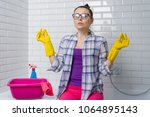 woman cleaning in the bathroom... | Shutterstock . vector #1064895143