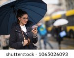 happy young woman waiting a bus ... | Shutterstock . vector #1065026093