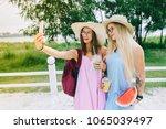 two happy girls drink juice | Shutterstock . vector #1065039497