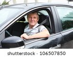 Fastened smiling Caucasian senior man sitting in car on driver seat - stock photo