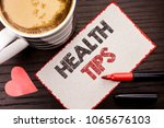 Small photo of Text sign showing Health Tips. Conceptual photo Healthy Suggestions Suggest Information Guidance Tip Idea written on Sticky Note on the wooden background Coffee Cup Heart Marker next to it.