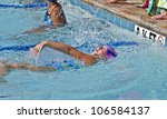 A young girl swimming backstroke during a competition swim meet. - stock photo
