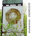 Small photo of Pripyat, Kyiv region / Ukraine - April 28 2008: soviet communist and socialist lopsided rusty artifact on the main square of the abandoned town. Featuring leader Lenin, hammer and sickle, cones.
