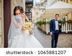 beautiful bride hides her face... | Shutterstock . vector #1065881207
