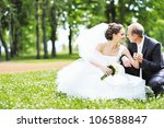 happy bride and groom in a park.... | Shutterstock . vector #106588847