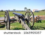 Small photo of An American Civil War cannon points toward the west at Gettysburg National Military Park. In the distance is the historic Abraham Trostle Farm as it stood in 1863.