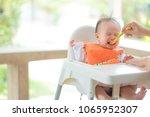 mother feeding adorable baby...   Shutterstock . vector #1065952307