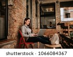 young woman using laptop while... | Shutterstock . vector #1066084367