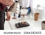 Small photo of A man is preparing coffee by a method of transfusion.
