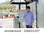 A Young Asian Man At A Bus Sto...