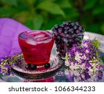 Small photo of Composition from berries of Aronia in a glass on a metal tray. Berries of Aronia in a glass cup. Compote with ice