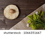 Small photo of egg on a round wooden spile next to a bouquet of yellow flowers lying on a wooden background