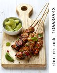 Thai chicken skewers with lime and chili, on wooden board. - stock photo