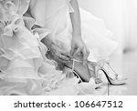 The bride is putting on her shoes for the wedding day. - stock photo