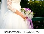 Bride holding wedding flowers. - stock photo