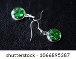 green resin earrings on a dark... | Shutterstock . vector #1066895387