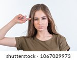 Small photo of beautiful brown-haired woman with long hair with a prudent expression, a concept of female emotions