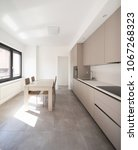 Small photo of Minimal kitchen in a modern apartment with chairs and table. Nobody iniside